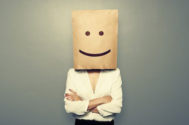 Woman with brown bag over her head with a smiley face on it