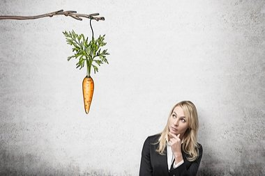 woman looking at carrot on the stick