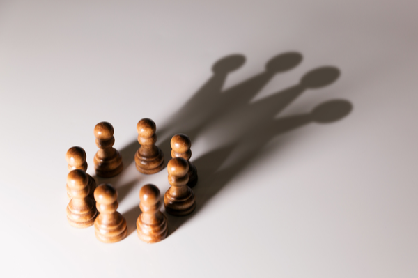 Chess pieces in the shadow of a crown