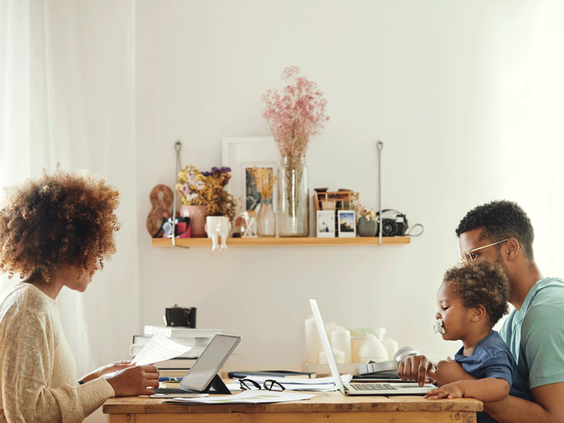 Adults sitting at table working flexibly with small child