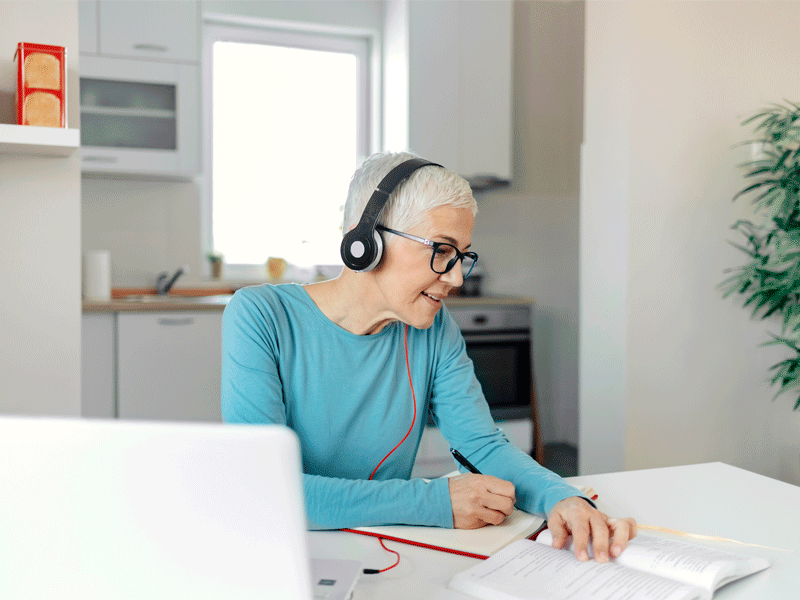 Lady studying remotely at home on laptop with headphones