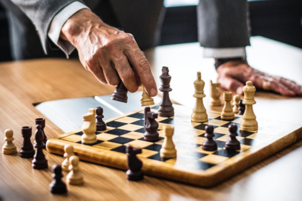 Man moving a piece on a chess board