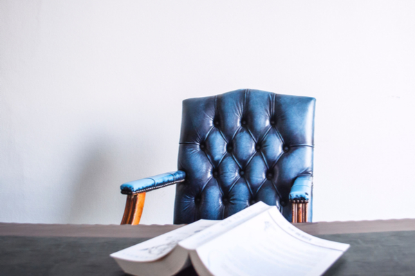 a book on a table with a leather chair behind it