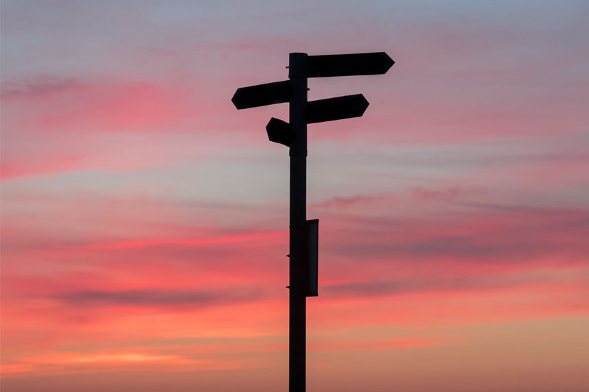 Signpost in front of sunset