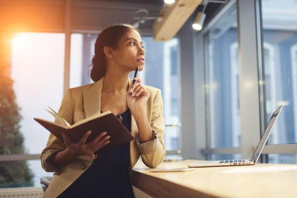 Woman with book open thinking