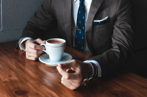 Man in a suit with a small cup of coffe