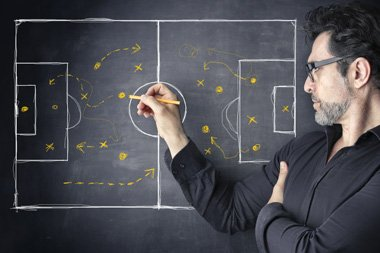 Man drawing a football pitch on a blackboard showing strategy