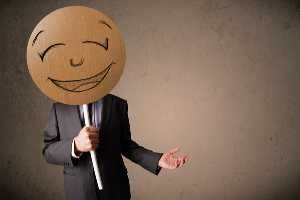 Businessman with hiding his face behind happy face mask