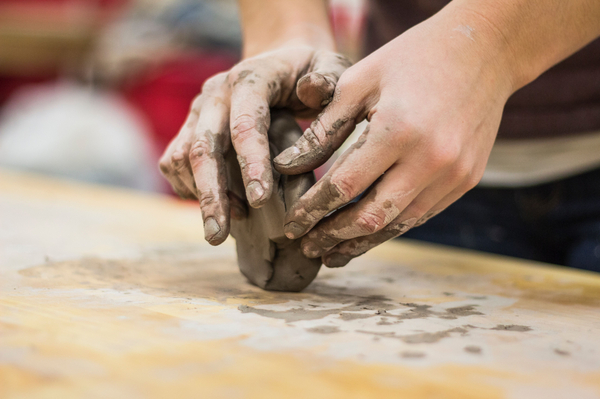 person rolling clay