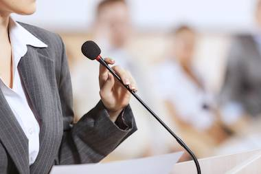 Woman in a suit in front of a microphone