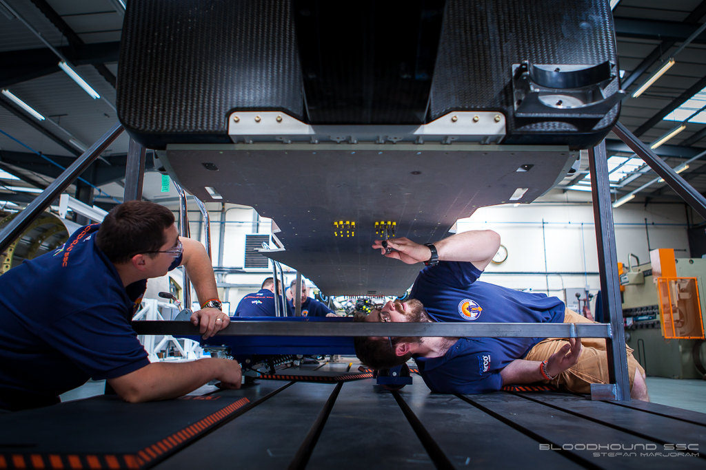 mechanics working on the underside of a car