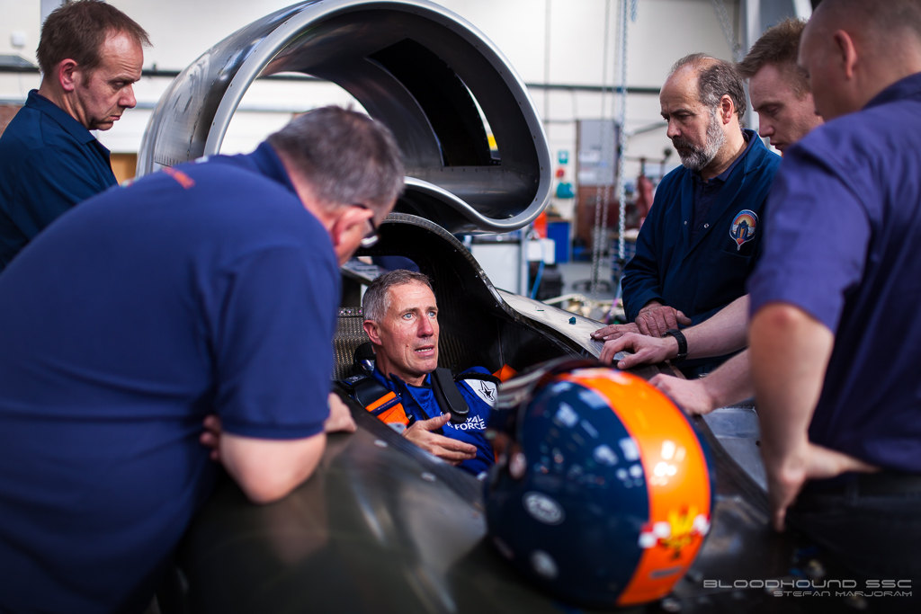 mechanics talking to driver in cockpit