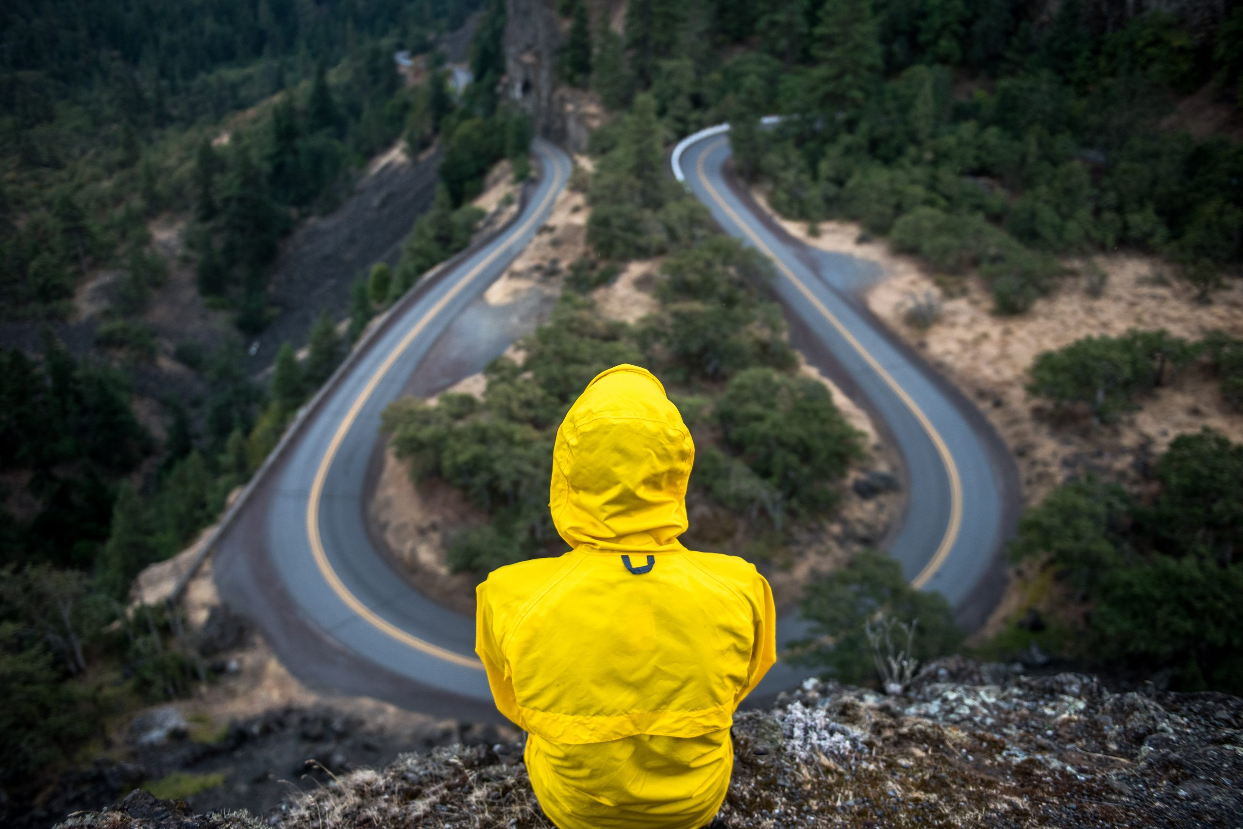 Person in yellow jacket sitting on a cliff overlooking a road