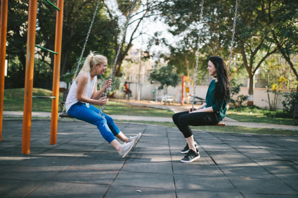 two women sitting on swings facing each other