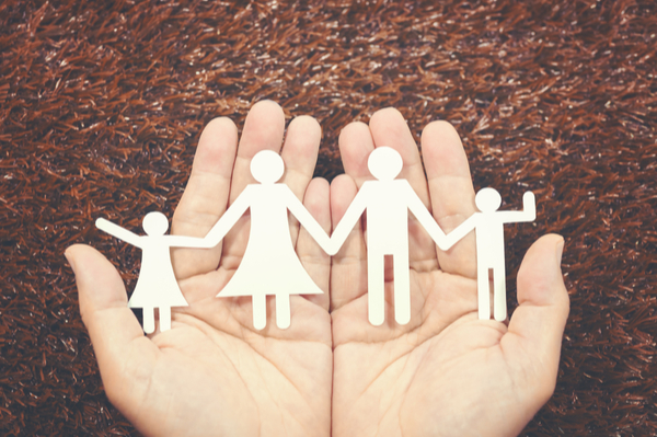 hands holding a paper family