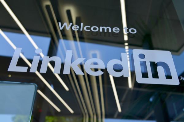 LinkedIn logo in white on a glass window