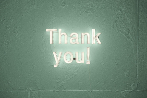 neon type letters on a wall spelling thank you