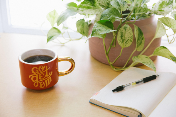 a cup of tea or coffee next to a plant, a pen and pad of paper