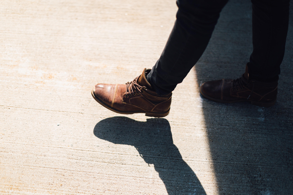 a person's legs taking a step from the shade to sunlight