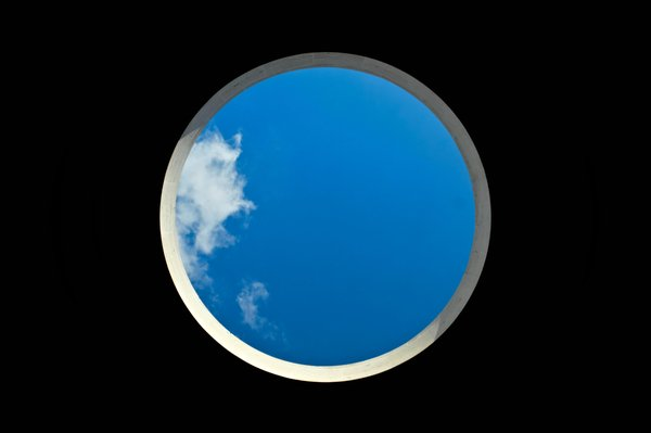 a blue sky with some clouds on the left within a circular shape