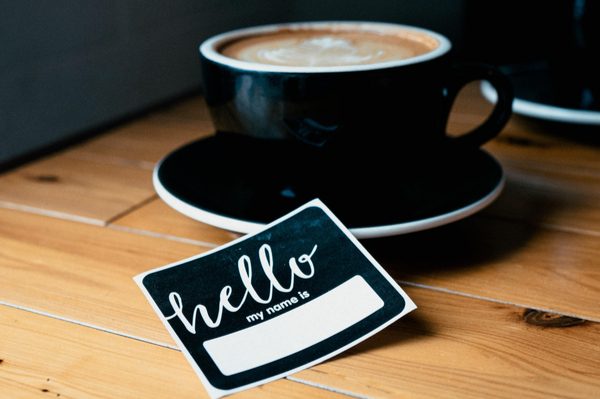 "a black teacup with a ""hello my name is"" sticker laying in front"