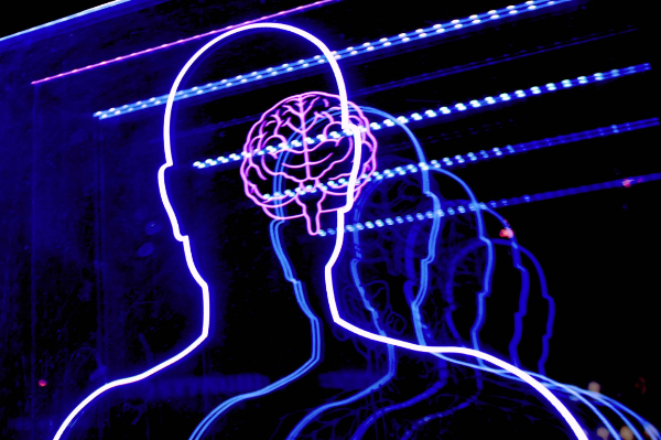 a neon outline of a human head and shoulders with a brain inside the head