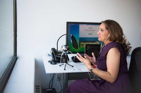 a woman sitting at a desk talking on a virtual meeting
