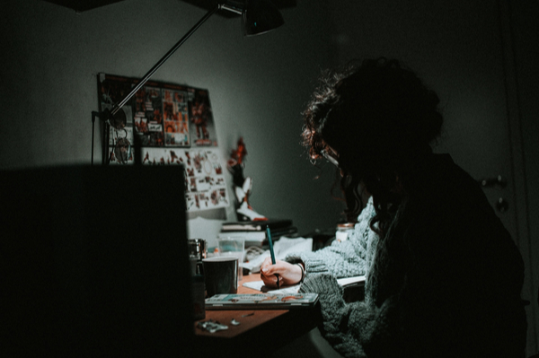 a person writing at a lit desk in a darkened room