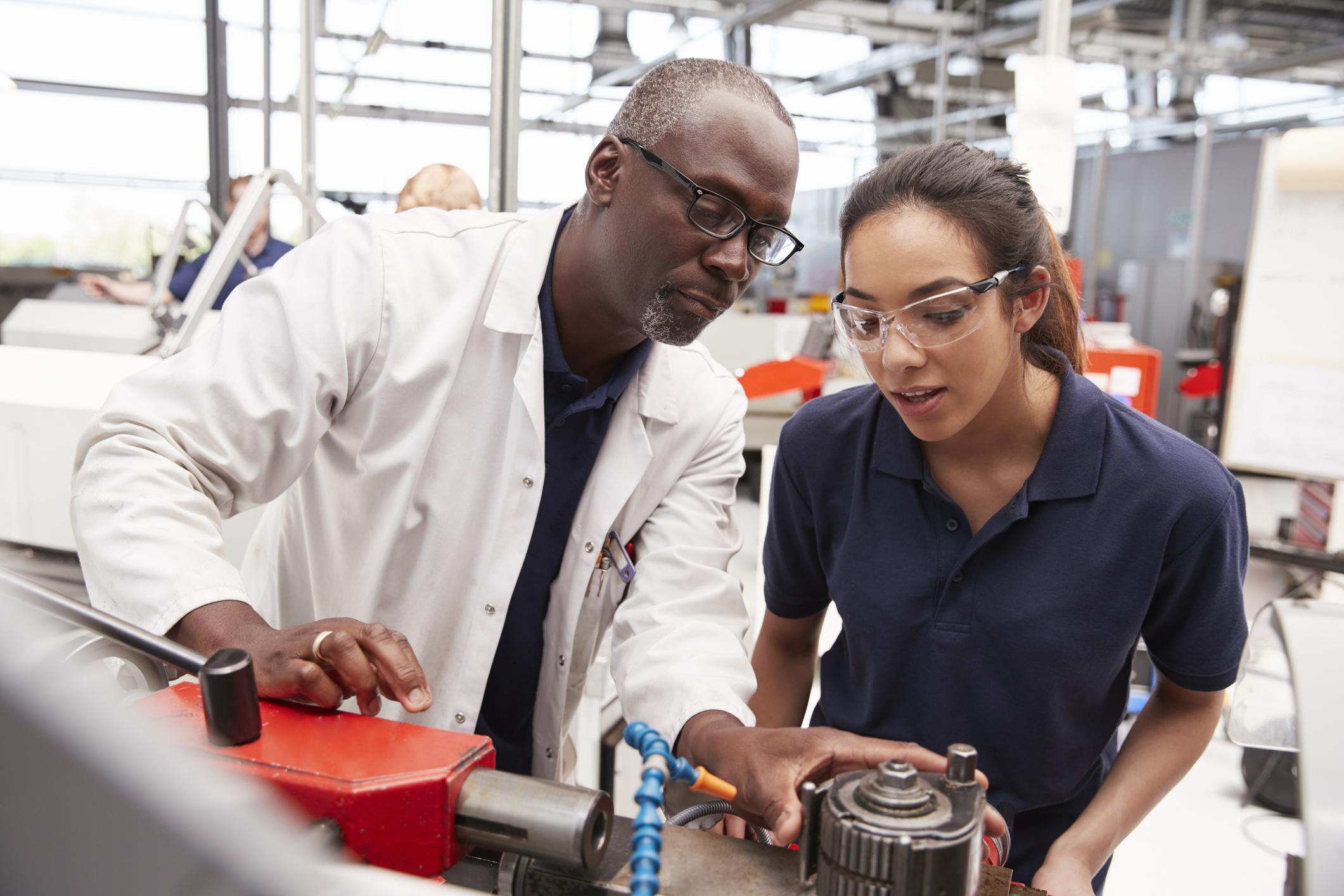 Engineer showing equipment to a female apprentice, close up