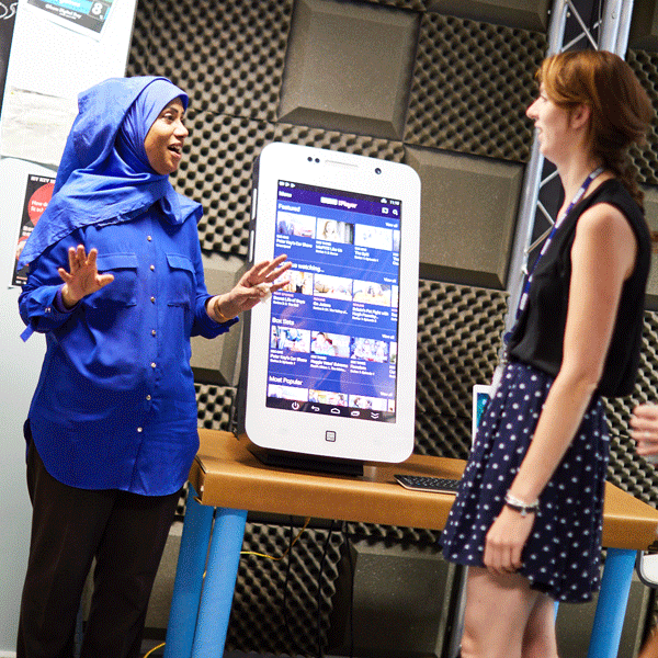 Woman in blue speaking to another woman in front of large touch screen