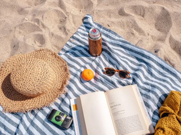 Beach towel on the sand, with a hat, book and sunglasses