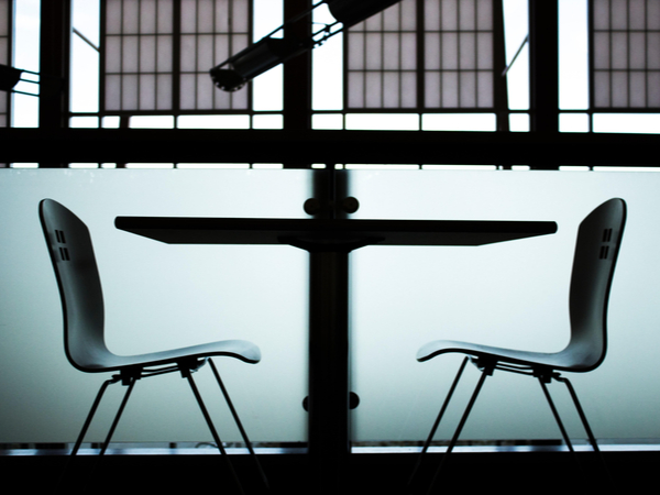 Two empty chairs across a table