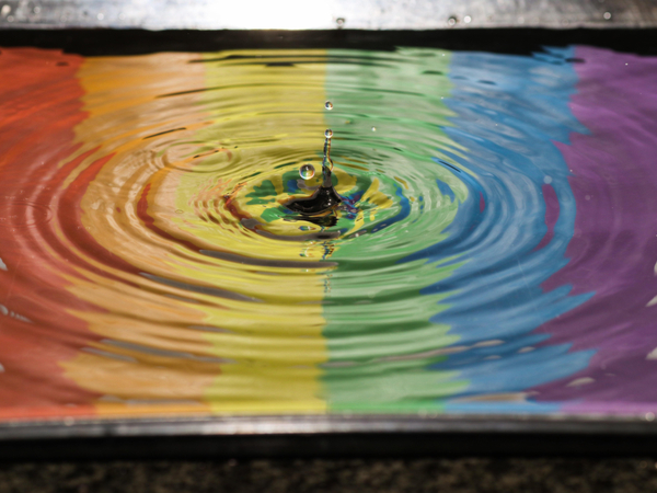LGBT+ flag reflected in a body of water