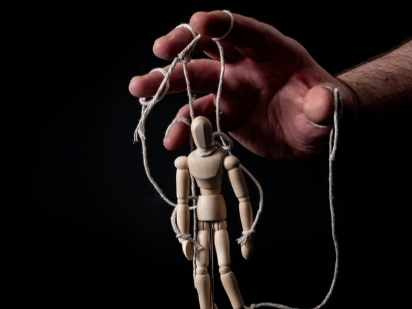 Hands controlling marionette puppet