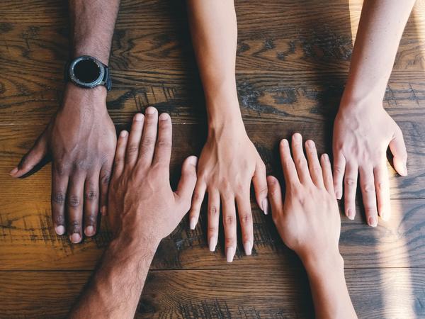 Hands of different ethnicities on a table