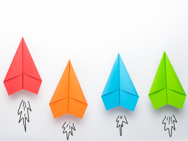 Four different-coloured paper aeroplanes against a white background