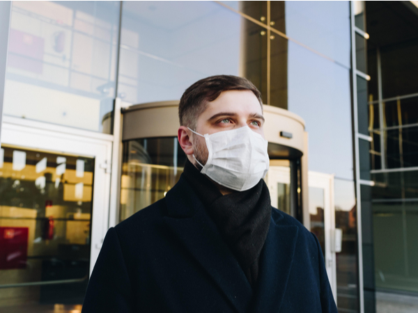 Person in face mask outside of workplace