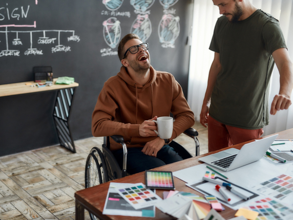 Two colleagues, one in a wheelchair, talking at work
