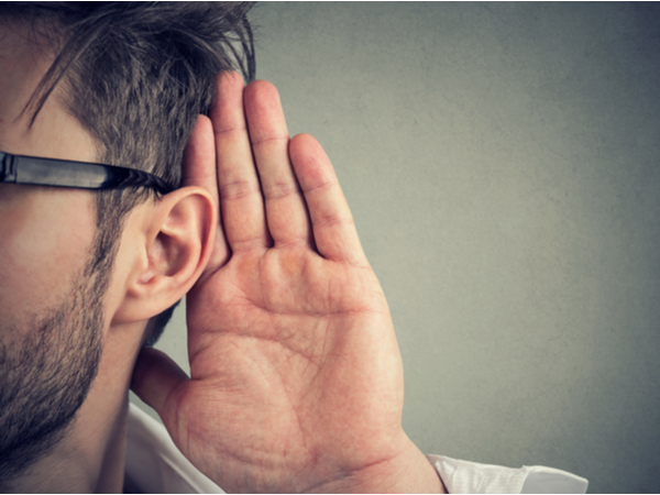 A person listening with their hand to their ear