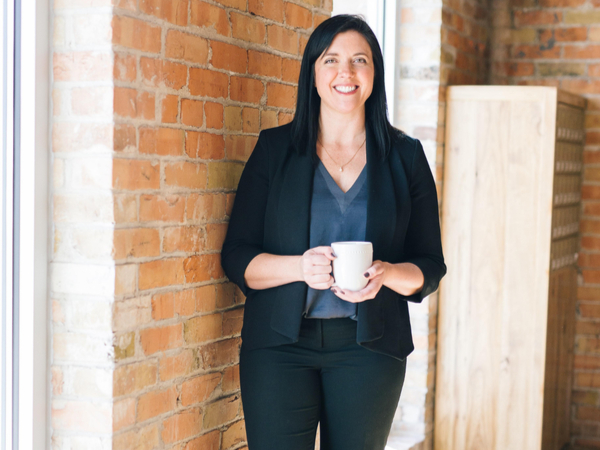 Woman holding a coffee cup and looking into camera