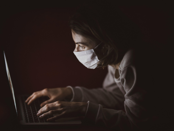 Person in. mask at laptop