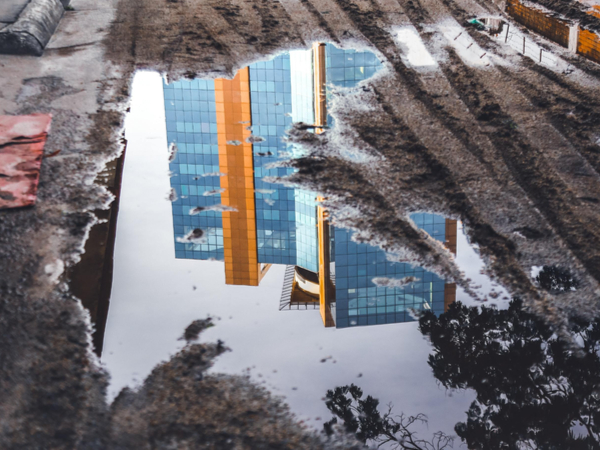 Buildings reflected in puddle