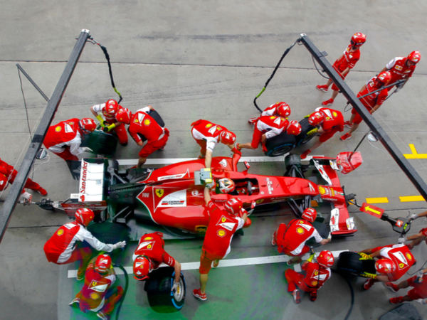 F1 team collaborating in the pit during a race