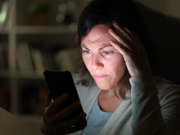 Person's face illuminated by phone screen, looking sad