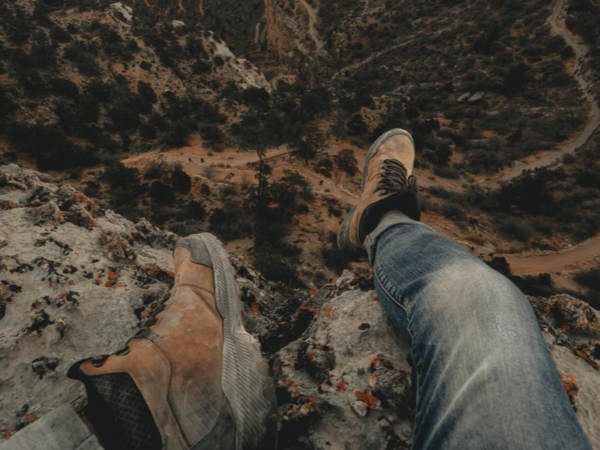 Pair of feet dangling over cliff edge