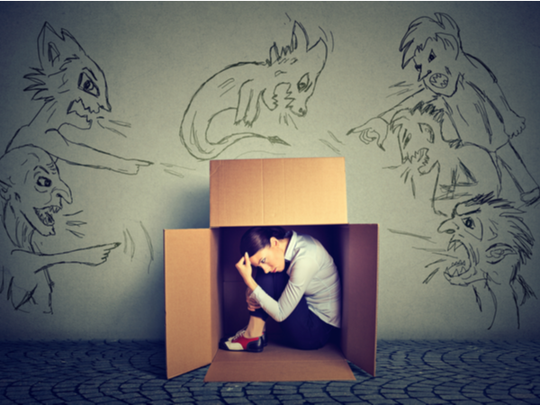 Woman hiding from inner demons in a box