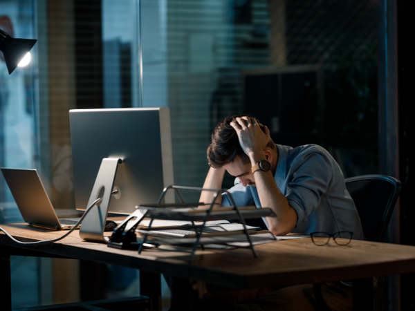 Person at their desk with their head in their hands