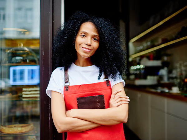 Female business owner stood happily outside business