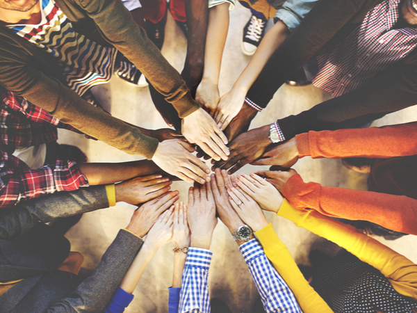 Hands of colleagues stacked in a team huddle