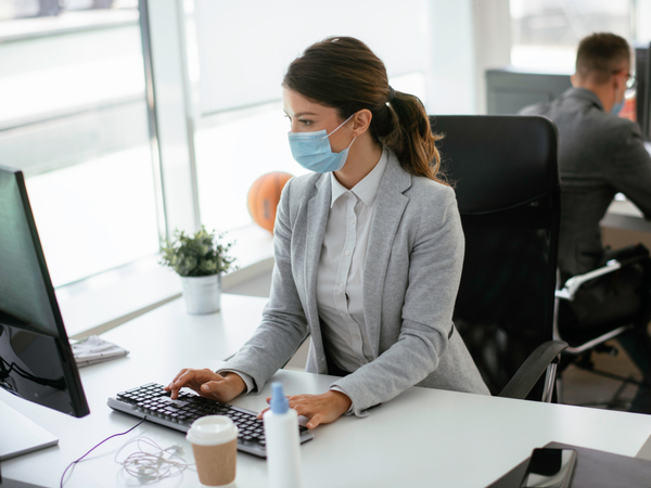 Person workiing iin an office with face mask on